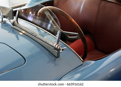 Detail of hood with windshield and steering wheel of blue car