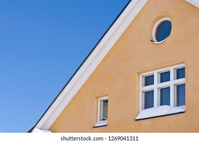 Detail of house exterior against blue sky.
