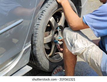 Detail image of hands with tool, changing tyre of car