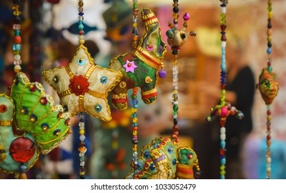 Detail of indian hanging elephants and other figures in a hippie street market in Ibiza. A person in the background with bokeh. Las Dalia flea market, Ibiza, Spain.