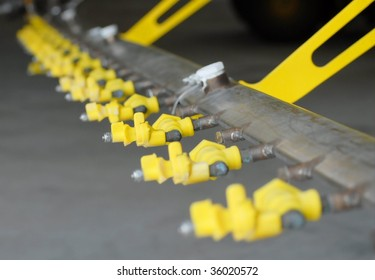 Detail of industrial agriculture crop duster sprayers. The spray nozzles are yellow.  The perspective is looking down the line of spray nozzles. Shallow depth of field focuses on the third nozzle