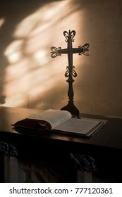 Detail from the interior of a church with a decorative cross on a stand and Bible on table, lit from side glass window.