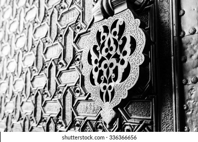 Detail of an islamic door knocker and ornaments outside one of the main entrance gates to the Cathedral of Seville, Spain. Shallow DOF, toned.