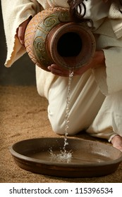 Detail of Jesus pouring water on a neutral background