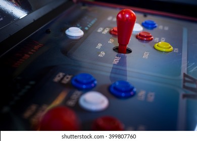 Detail of a joystick and buttons on an old arcade game in a gaming room