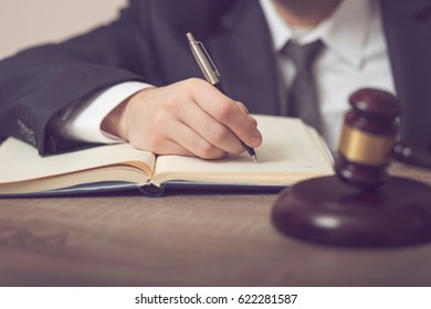 Detail of a judge sitting at his desk, studying new laws and legislation and taking notes. Selective focus