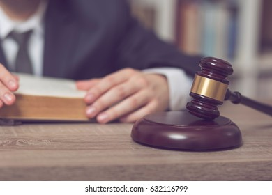 Detail of a judge sitting at his desk, studying new laws and legislation. Selective focus