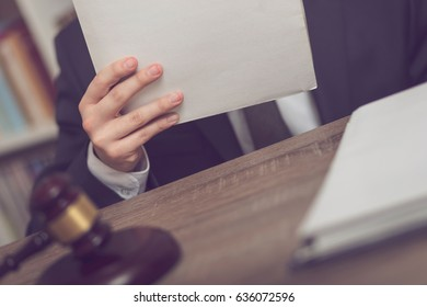 Detail of a judge sitting at his desk, holding a file with a new case and studying it. Selective focus