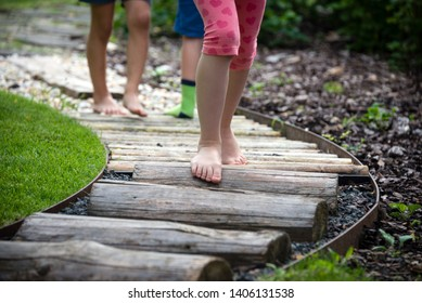 Detail of kids legs walking on wooden pathway barefoot