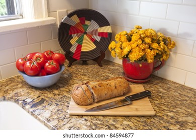 A detail in a kitchen of tomatoes, a potted plant, decorative plate and bread on a cutting board