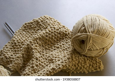 detail of knitted stiches in soft cotton yarn, grey background
