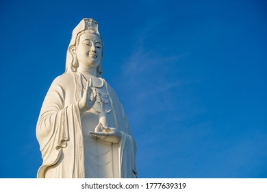 Detail of Lady Buddha statue in a Buddhist temple and blue sky background in Danang, Vietnam. Close up, copy space