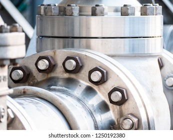 detail of large industrial steel flanges, full of bolts, on a line of high pressure fluids