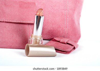 Detail of lipstick and Assortment of pink handbags on white background