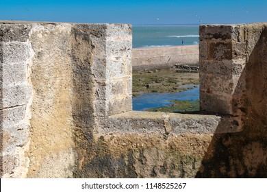Detail of the loophole in the former portuguese fortress in El Jadida, Morocco. View on the Atlantic ocean. Silhoutte of a person in the background. Blue sky.