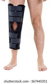 Detail of Lower Half of Man Wearing Supportive Leg Brace in Studio with White Background with Copy Space