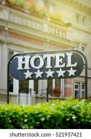 """Detail of a luxury five stars hotel with beautiful building in the background on a beautiful sunny day. Tilt shift lens used to accent the word """"hotel"""" and to emphasize the background"""