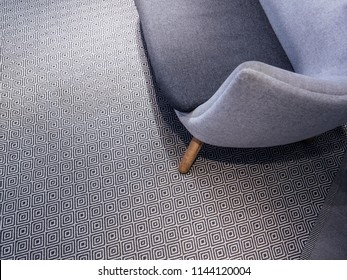 Detail of luxury sofa on wooden legs on beautiful carpet with seamless pattern - elevated view