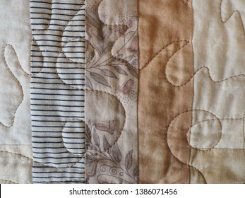 Detail of Machine Quilting on a Log Cabin Patchwork Quilt in Beige Colors
