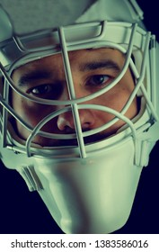 Detail of a male face in a white goalie hockey mask.This is a detail hockey goalie. He is concentrated on game.