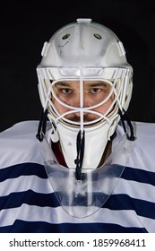 Detail of a male face in a white goalie hockey mask and  colorful lights.This is a detail hockey goalie. He is concentrated on game. He has colorful lights under his head.