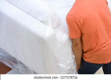 Detail of man carrying sofa into new home on moving in day