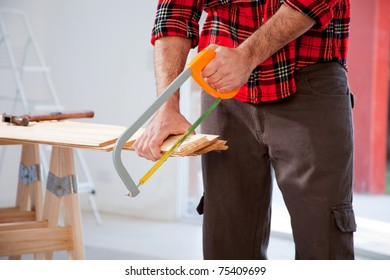 A detail of a man cutting wood with a small hand saw