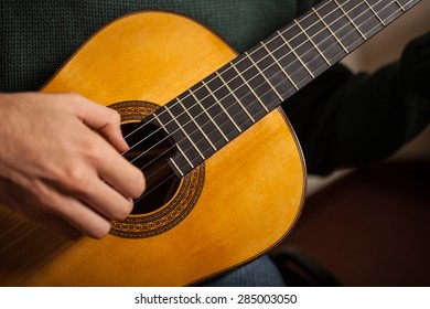 Detail of a man playing a guitar