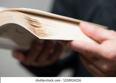Detail of man reading a book with dogears bookmarks.