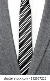 detail of a man wearing a gray jacket suit, white shirt and black and white striped tie