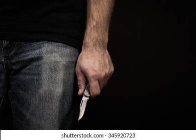 Detail of a man wearing jeans and a t shirt holding a pocket knife at his side