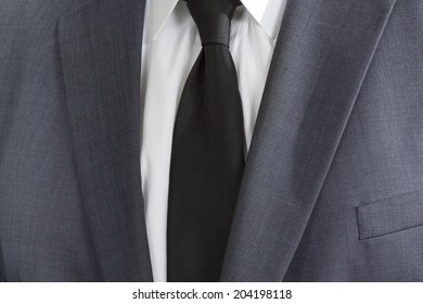Detail of a man wearing a suite with white shirt and black tie
