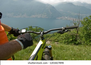 detail of man with yellow electric bicycle, e-bike, ebike, mountains, valley, lake of Como, summer, sport, adventure, sun, alps, Lombardy, Italy