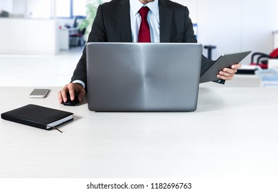 Detail of a manager at work at his laptop in an office