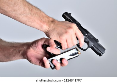 Detail of man's hand reloading pistol after shooting