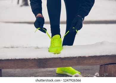 Detail of man's legs jogging in the park at snowy time.