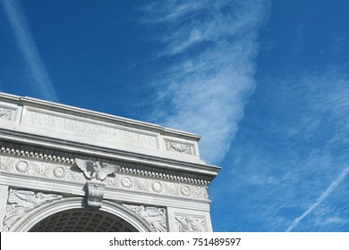 Detail of the marble arch in Washington Square Park, against a blue sky with light clouds