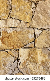 Detail of a masonry wall with irregular of orange color stones