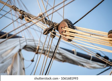 Detail of mast of ship. Detailed rigging with sails. Vintage sailing ship block and tackle. handmade woodwork statues and a forest on boat masts