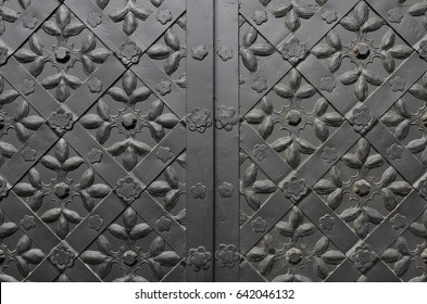 Detail of medieval black door with metal decoration of orthodox church, background, closeup