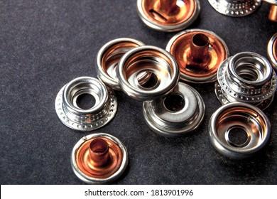 Detail für Metallknöpfe für Kleidung auf schwarzem Hintergrund.