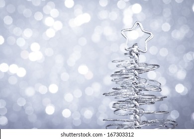 detail of metallic modern christmas tree on wood table on silver tint light bokeh background with space for text