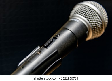 Detail of a microphone on the holder with a on off button on the body