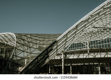 Detail of the milano trade fair architecture, roof swoops down to the ground level with clear blue sky backgrouns no clouds