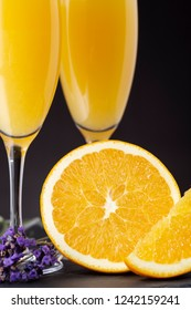 Detail of mimosa cocktails in champagne glasses with orange juice and sparkling wine decorated with lavender leaves and orange slices. Selective focus on the orange half