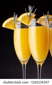 Detail of mimosa cocktails in champagne glasses with orange juice and sparkling wine decorated with lavender leaves and orange slices. Focus on the orange slice on the the glass