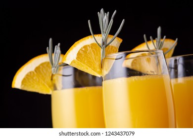 Detail of mimosa cocktails in champagne glasses with orange juice and sparkling wine decorated with lavender leaves and orange slices. Selective focus on the orange slice on the the glass