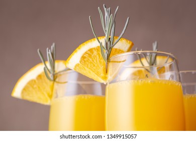 Detail of mimosa cocktails in champagne glasses with orange juice and sparkling wine decorated with lavender leaves and orange slices