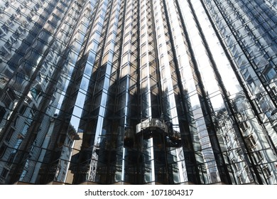 Detail of mirrored glass building facade with reflections of nearby buildings