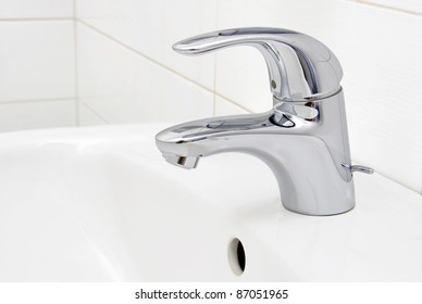detail of a modern ceramic hand wash basin with chrome water mixer tap